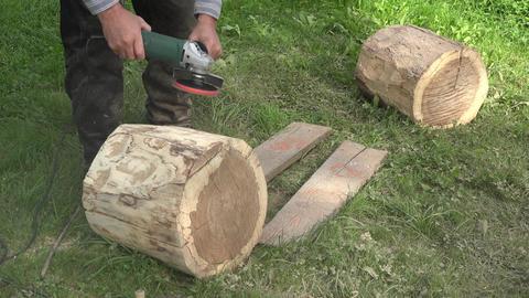 Sculptor prepare tree log wood for art work. Sanding bark with sander tool. Clos Footage