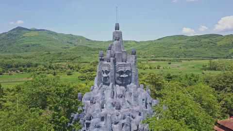 Flycam Rotates above Huge Sculpture among Trees in Highland Footage