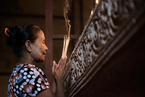 Asian woman praying with incense sticks Photo