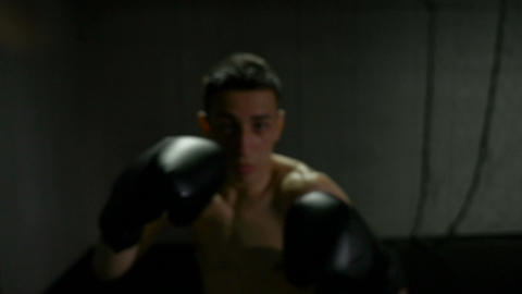 Slow motion point of view of young fighter wearing black gloves training himself Footage