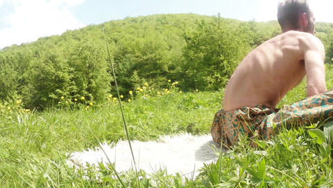 Back of a man sitting on a goat's skin in green grass in…, Live Action