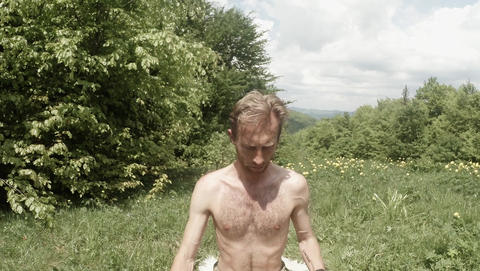 Man sitting trying to do yoga in the forest against the background of clouds Filmmaterial