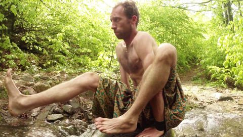Man is engaged in yoga on his hands on a stone in the middle of a creek in a den Footage