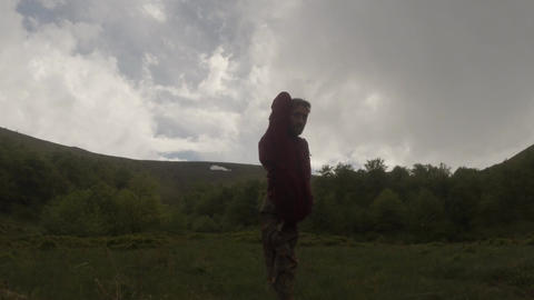 A man tries to stand on one foot pose tree in the rain in the woods in the mount Footage