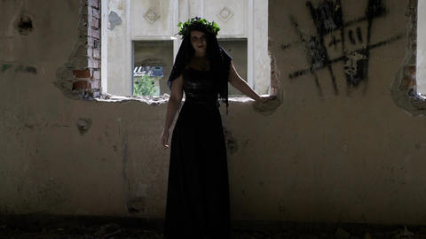 Vengeful spirit of woman in black vintage clothes standing near a ruined window  Footage