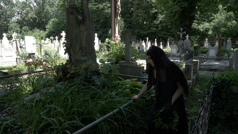 Pained funeral woman widow placing a crown on old grave with statue covered in m Footage