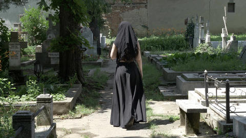 Creepy woman walking in cemetery alley to beloved grave and placing a crown on g Footage