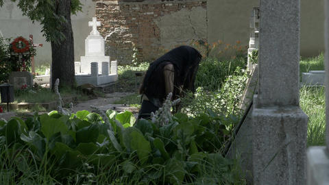 Crying woman in black mourning dress at the grave of beloved feeling desolation  Live Action