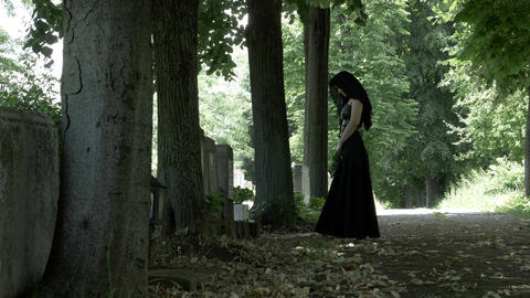 Suffering mourning woman in funeral dress on her knees at the grave of her dead  Footage