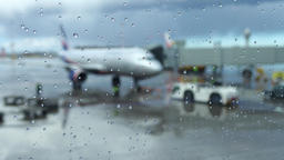 Passenger airliner prepared to departure, blurred view through wet glass Footage