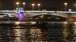 Small motor boat floats the river in night city in front of bridge Footage