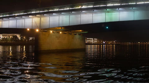Boat floats the river under bridge in city night. Camera inside boat Footage