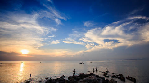 Silhouettes in Sea by Rocks Boats Sun from Behind Clouds Footage