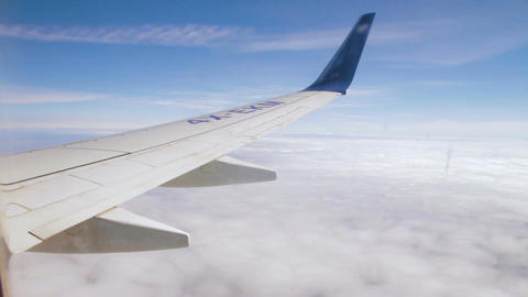 Airplane wing on the sky and over sea with clouds Footage