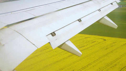 Airplane wing during landing with flaps down on the sky over land Live Action