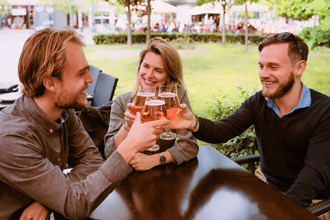 Group of smiling young friends clang glasses of beer Foto