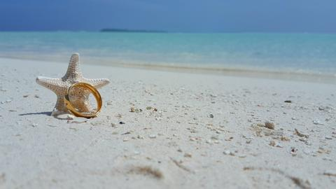 P00791 Maldives white sandy beach wedding engagement gold ring on sunny tropical Foto