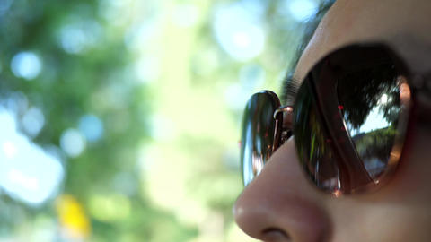 Motion of woman wears sunglasses eyes looking on road with blur traffic flow 4k  Footage