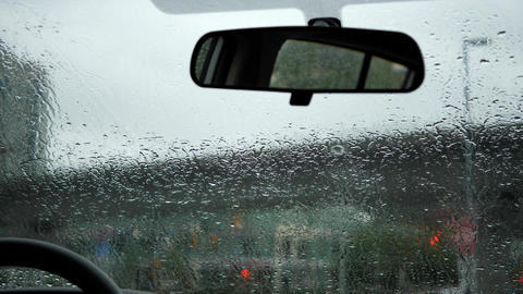Motion of rainy day view during car windshield wipers rain drops sliding down in Footage