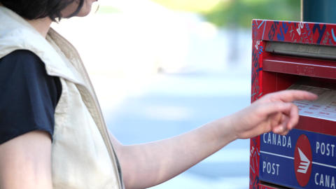 Camera following of woman placing mail in a canadian mail box with 4k resolution Footage