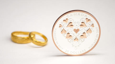 Motion of married in 2017 twenty dollars coin and two rings on white background Live Action