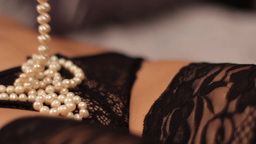 White beads on a woman's body in black erotic lingerie Footage