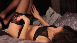 Sexy brunette girl in sexy lingerie lies on a bed Footage