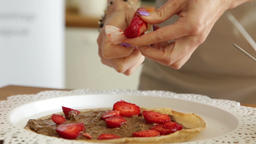 Putting berries on the first layer of pancake cake Footage