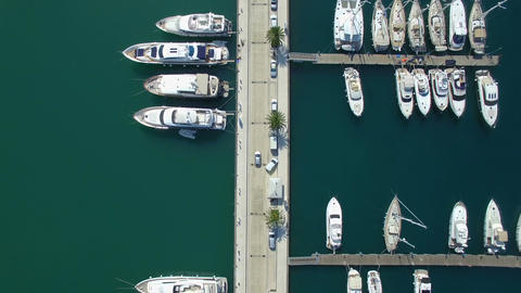Top view aerial footage of Porto Montenegro marina harbor pier with car moving a ビデオ