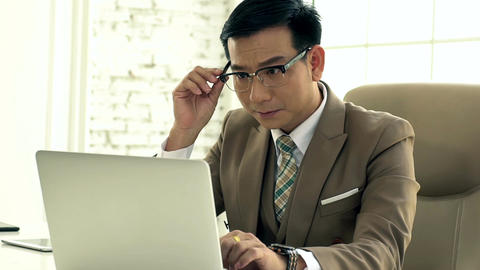 Asian Business man Working on a Laptop Intense Footage