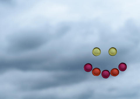 Smiley face made of candy contrasting with cloudy background Photo