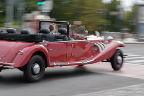 Old red speeding car riding on a street Foto