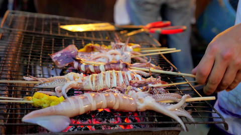 Barbeque Grilled fresh squid on charcoal stove Live Action