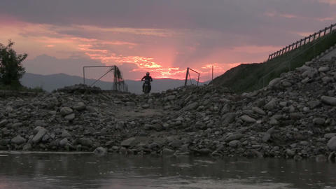 Competition riders, captured at sunset. It is filmed by a river. The route is on Footage