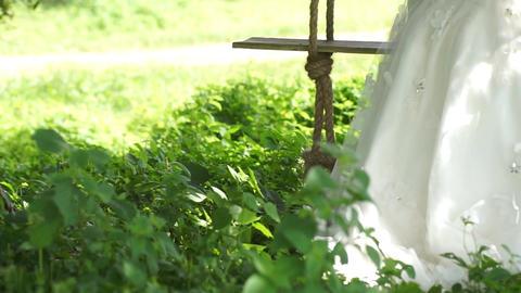 Bride Swinging Gently in a Garden on Summer Footage