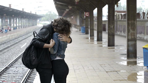 Young couple embracing and saying goodbye before boyfriend getting on train to l Footage