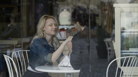 Loving boyfriend caressing his girlfriend and kissing her hand into a restaurant Footage