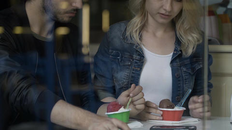 Teenage couple enjoying their first date talking and eating ice cream into a cof Footage