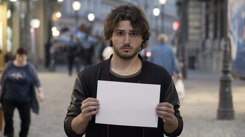 Sad young man holding a white copy space banner on the street Footage