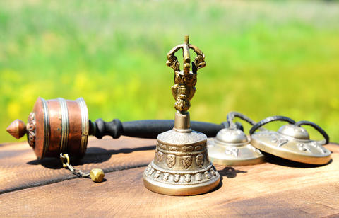 copper bell with Tibetan religious objects, close up フォト