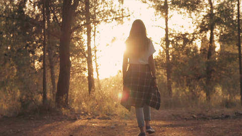Back view of young girl walking in the forest towards sunset Footage