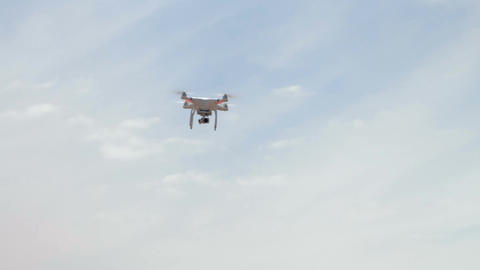 Quadrocopter flying overhead against a blue sky Footage