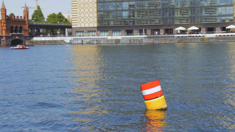 Yellow red and white steel navigational floating buoy in the blue Spree river wa ビデオ