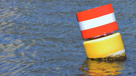 Yellow red and white steel navigational floating buoy in the blue Spree river wa Footage