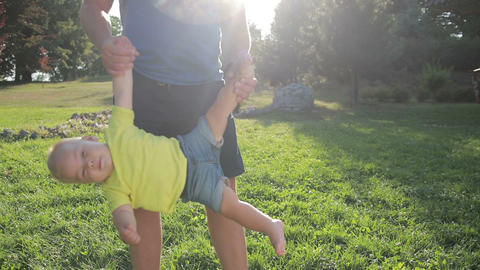 Father swinging toddler son upside down in park Footage