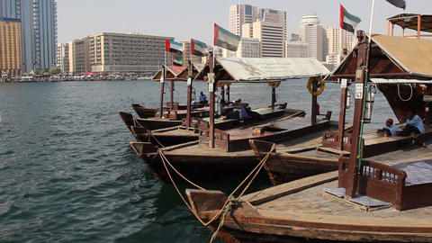 Empty Abra boats sway on waves, parked board to board, drivers rest in shadow Live Action