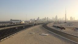 Large highway across deserted land, development area, Dubai skyline on back Footage