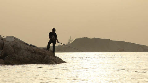 Unidentified man with fishing rod, contrast silhouette against light Footage