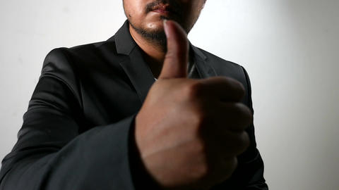 Hardwork sweating Serious Businessman in Black Suit showing thumbs up 画像