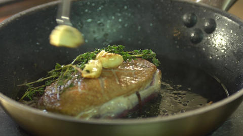 Chef cooks meat in a frying pan with seasonings Archivo